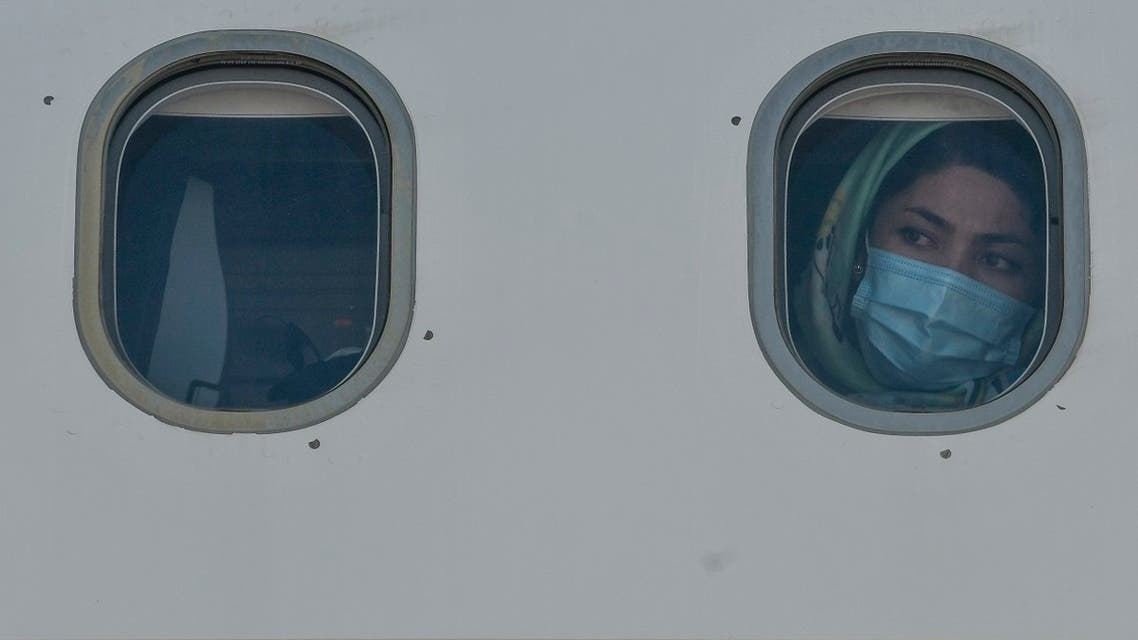 A woman form a group of 85 vulnerable refugees, mainly families with children with health problems, looks on from the windows of a plane after boarding for Germany as part of the EU relocation program from Greek islands' hotspots on July 24, 2020 at Athens' international airport in Spata. (AFP)