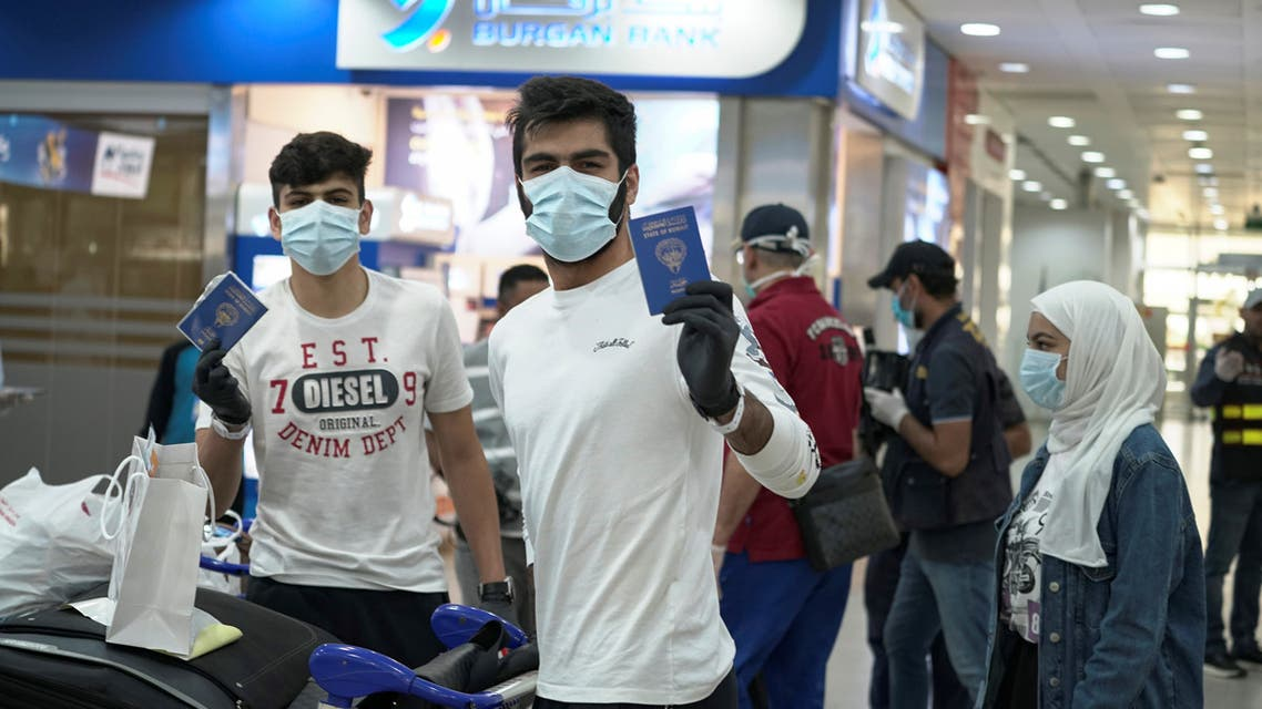 Kuwaiti boys wearing protective face masks and quarantine tracking bracelets, following the outbreak of the coronavirus, pose for the camera as they hold up their passports in Kuwait Airport, April 21, 2020. (Reuters)