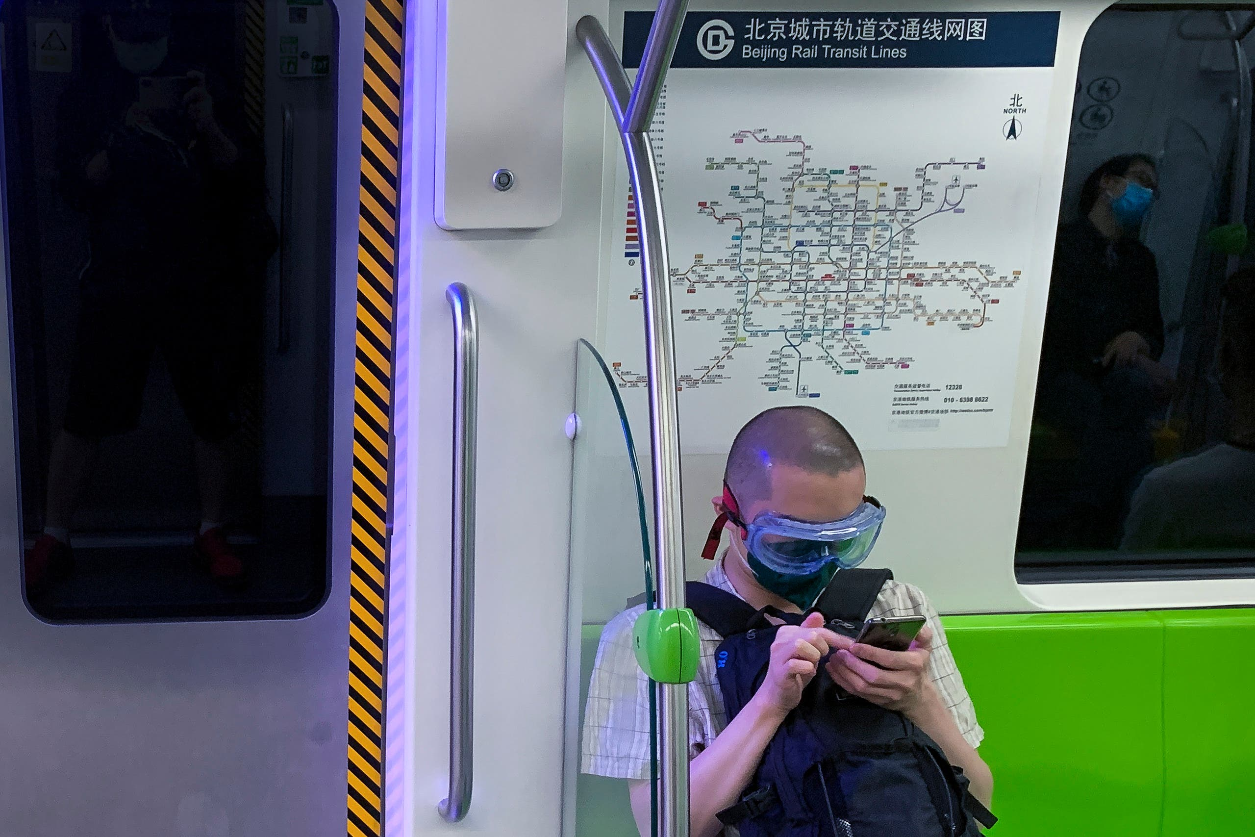 A commuter wearing a goggle and protective face mask to help curb the spread of the new coronavirus sits on the seat of a subway train in Beijing on June 16, 2020. (AP)
