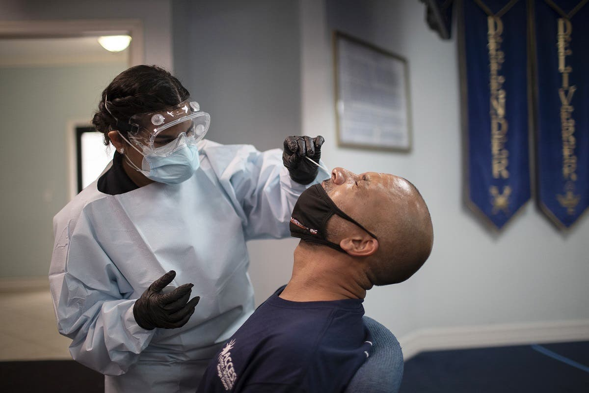 A health care worker use a nasal swab to test Eric Rodriguez for COVID-19 at a pop up testing site at the Koinonia Worship Center and Village on July 22, 2020 in Pembroke Park, Florida. (AFP)