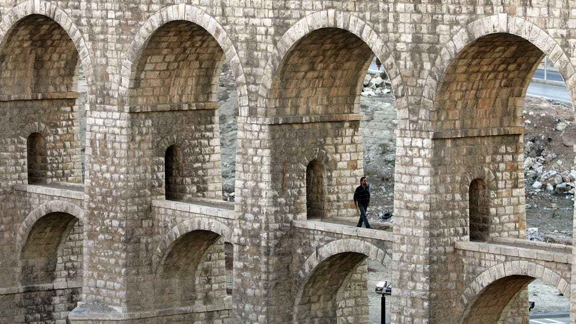A man walks under the Ten Bridges in Amman, Jordan, a structure part of the Hijaz Railway, which the Ottoman started building in 1908. (AP)