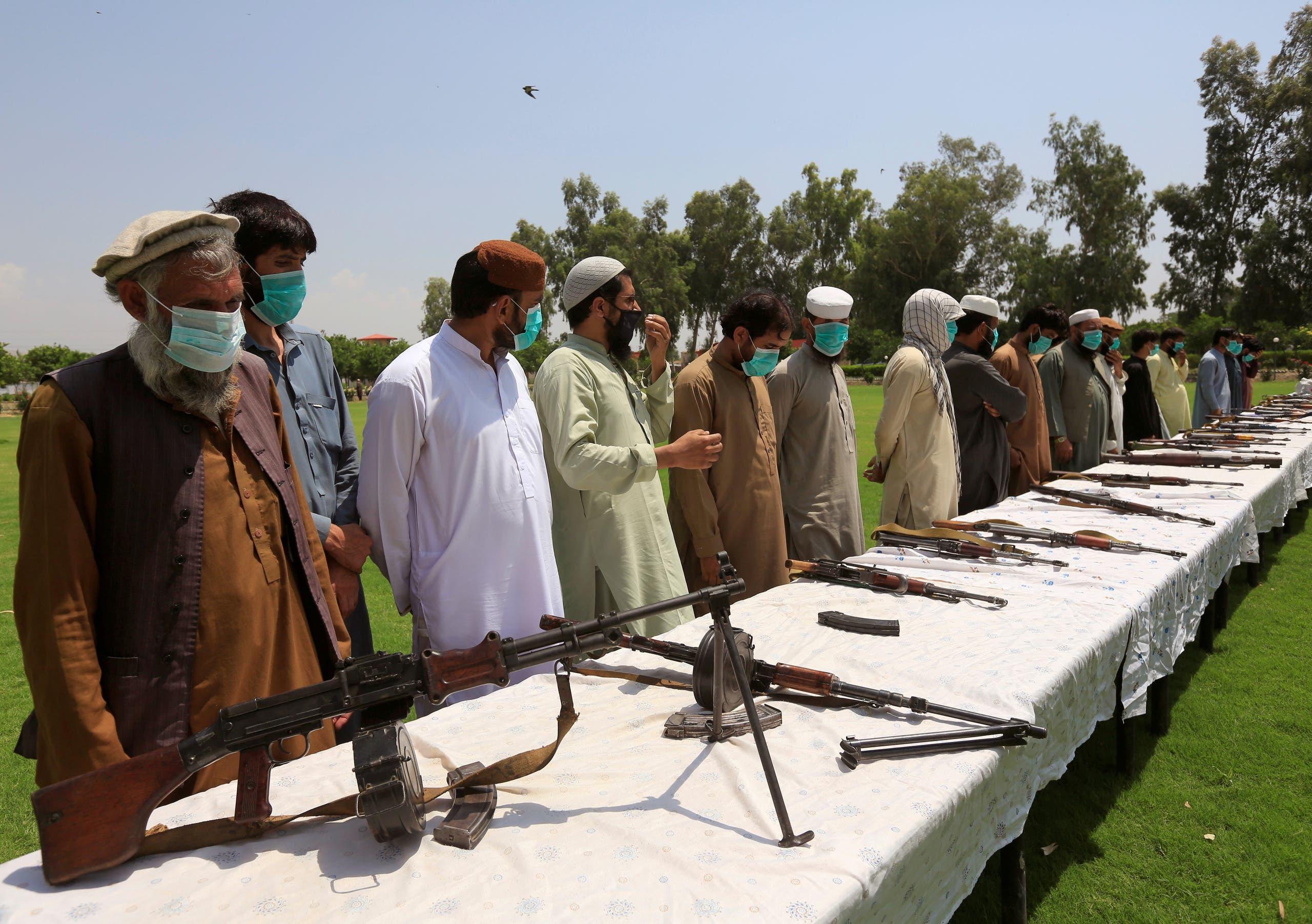 عناصر من طالبان يسلمون أسلحتهم للدولة في جلال أباد في يونيو الماضي ضمن عملية مصالحة