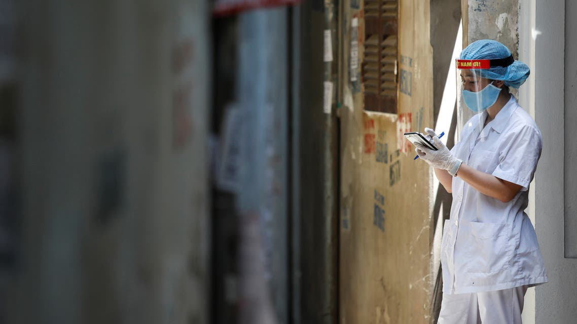 A healthcare worker is seen at a lane near the house of a coronavirus disease (COVID-19) patient while investigating infection links in Hanoi. (Reuters)