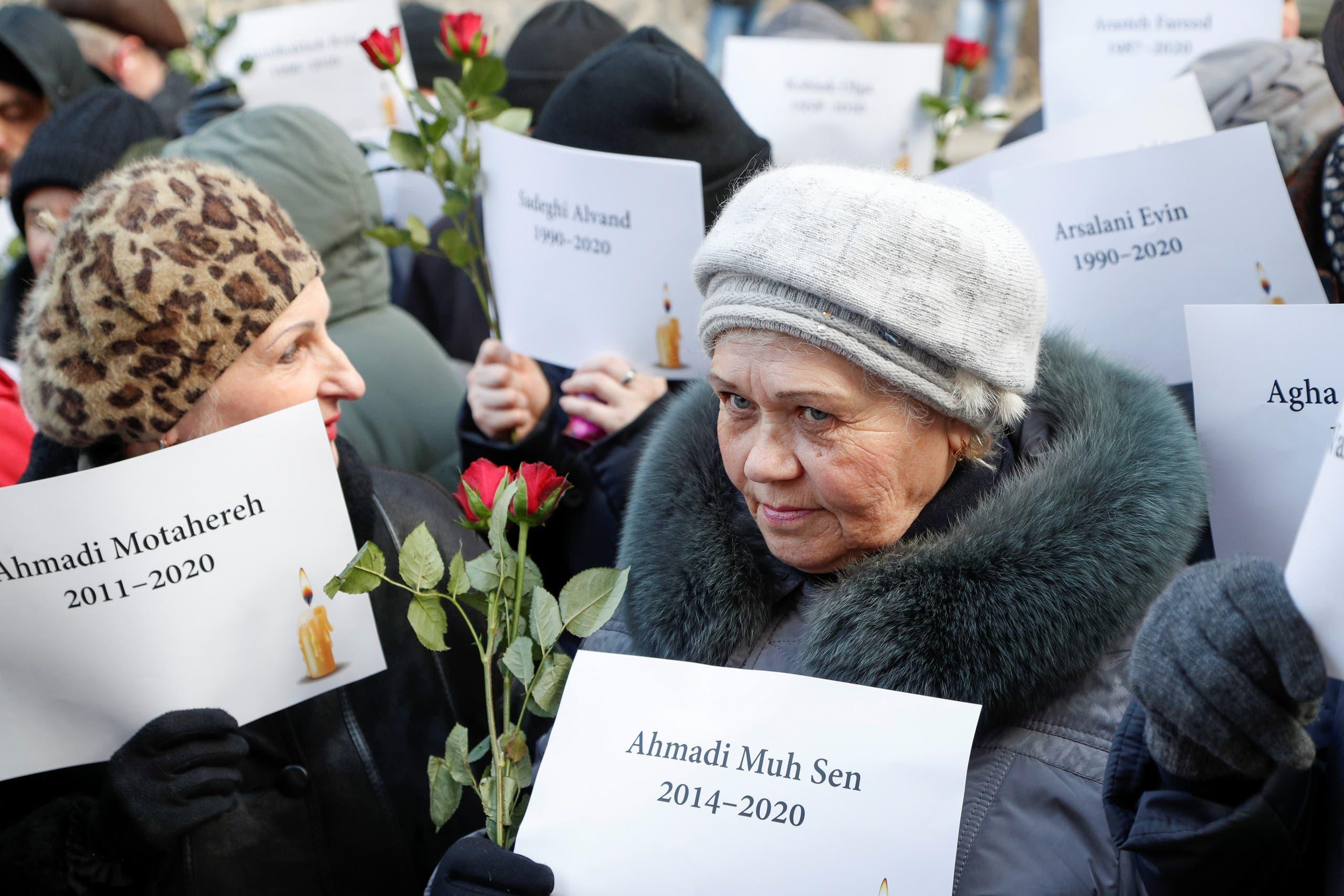 """أشخاص يحملون أسماء ضحايا الطائرة الأوكرانية """"أرشيفية"""""""