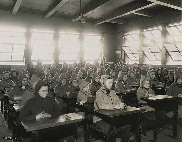 صورة لتلاميذ يرتدون معاطف داخل قسم مجهز بنوافذ عديدة لضمان تهوية جيدة