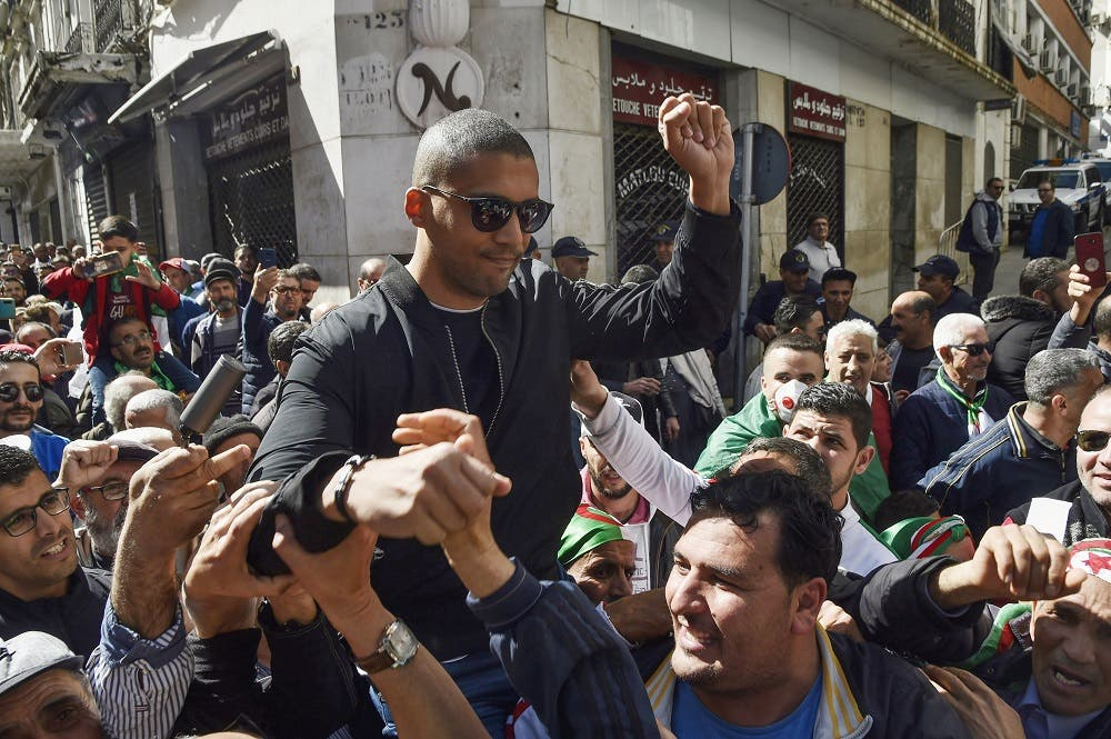 A picture taken on March 6, 2020 shows Algerian protesters carrying journalist Khaled Drareni on their shoulders. (AFP)
