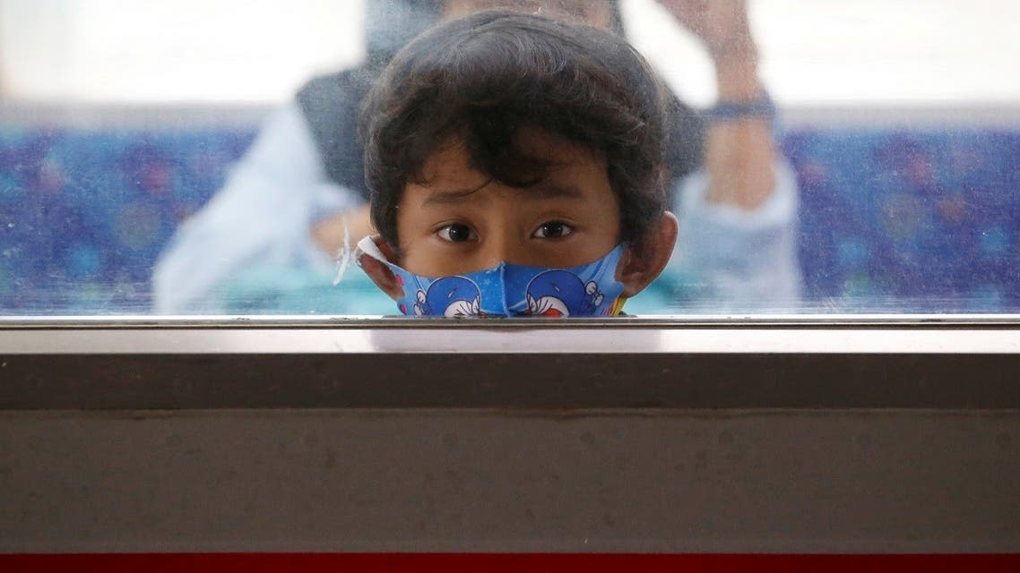 A child wearing a protective mask looks through a window while traveling with a commuter train, following the coronavirus disease (COVID-19) outbreak in Jakarta. (Reuters)