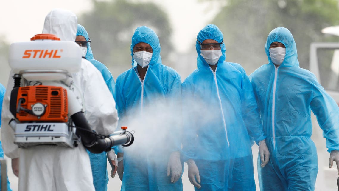 A health worker in a white protective suit sprays disinfectant at Vietnamese construction workers infected with the coronavirus disease (COVID-19), upon their arrival at the tropical diseases hospital after being repatriated from Equatorial Guinea via a specially-adapted Vietnam Airlines plane filled with medical equipment and negative pressure chambers, in Hanoi, Vietnam July 29, 2020. REUTERS/Kham