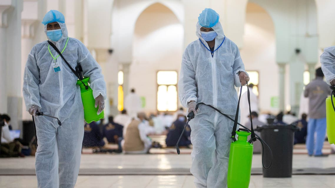 Health workers wearing personal protective equipment (PPE) disinfect the floor as Muslim pilgrims pray inside Namira Mosque in Arafat to mark Haj's most important day, Day of Arafat, during their Haj pilgrimage amid the coronavirus disease (COVID-19) pandemic, outside the holy city of Mecca, Saudi Arabia July 30, 2020. Saudi Ministry of Media/Handout via REUTERS ATTENTION EDITORS - THIS PICTURE WAS PROVIDED BY A THIRD PARTY.