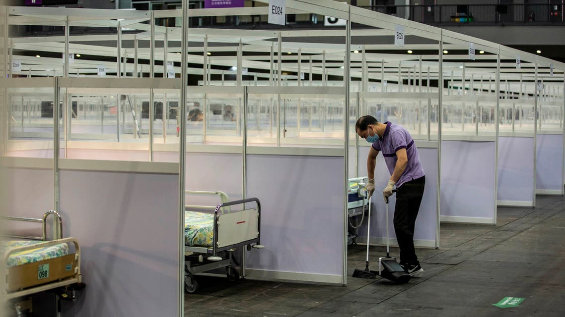 A worker cleans near rows of beds at a temporary field hospital set up at Asia World Expo in Hong Kong on August 1, 2020. (AFP)