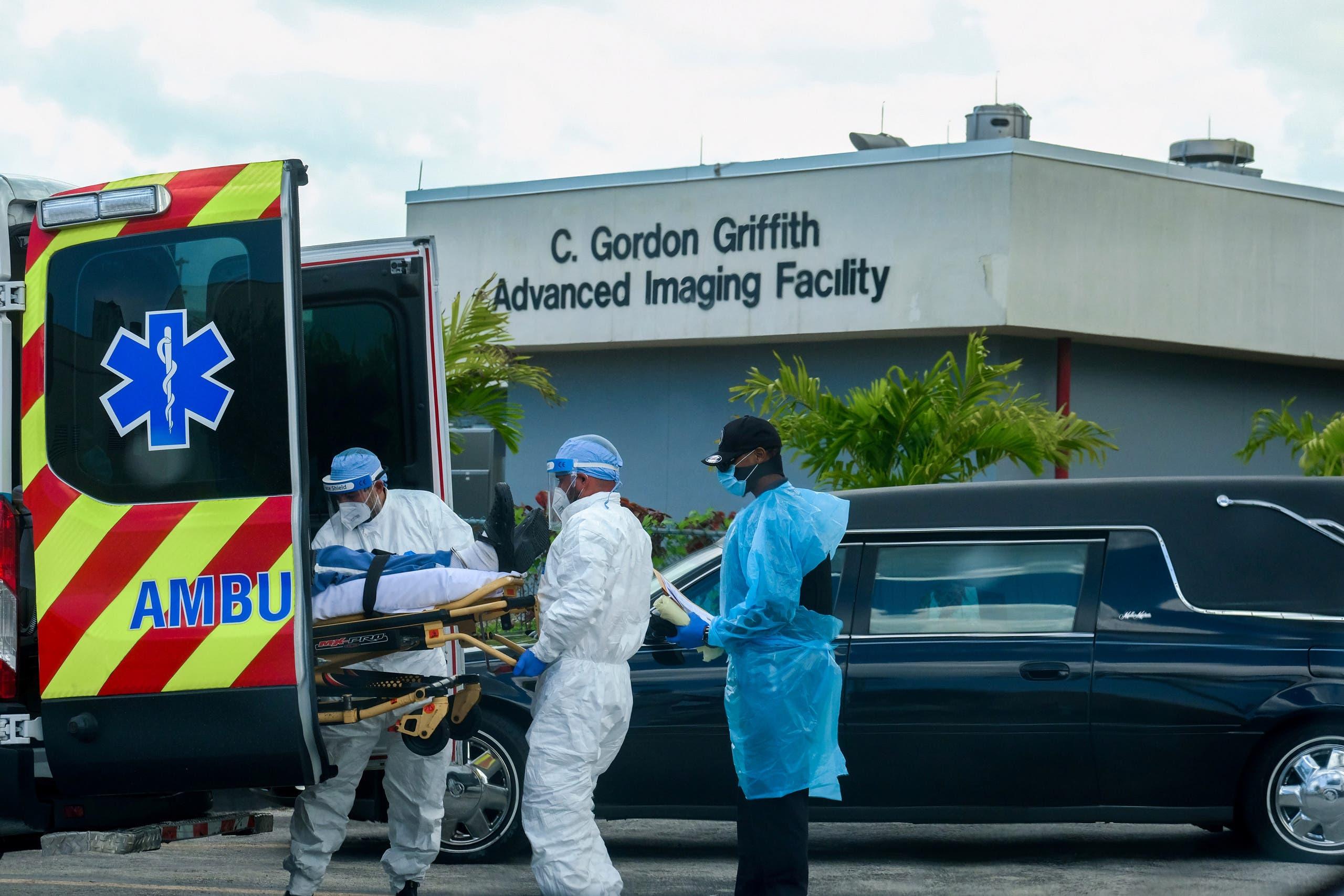 نقل مصاب بكورونا لمركز علاج في فلوريدا بينما تقف سيارة نقل الموتى أمام المركز