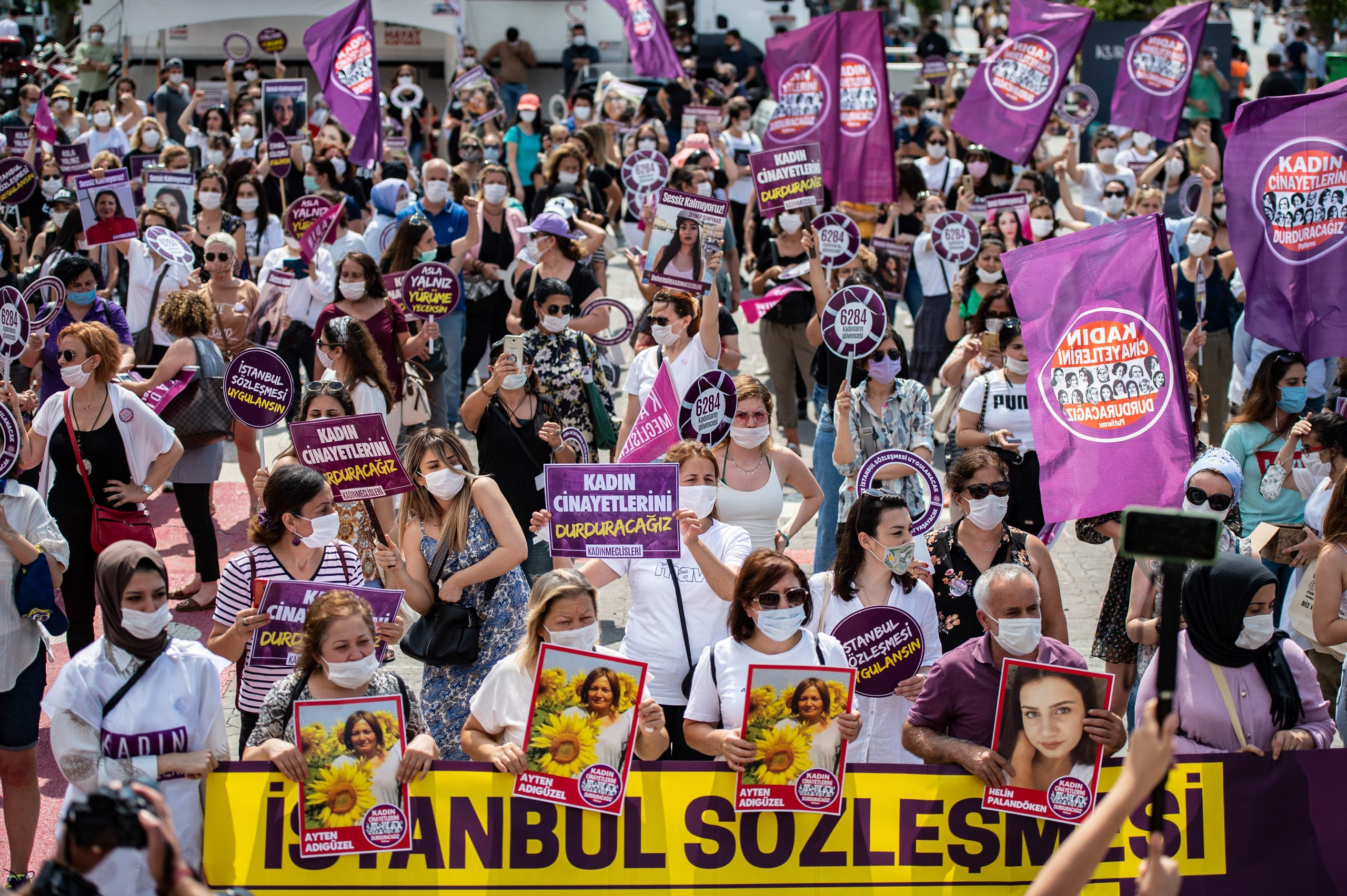 Demonstrators hold placards and portraits of women, during a protest for better implementation of the Istanbul Convention in Istanbul, Turkey. (AFP)