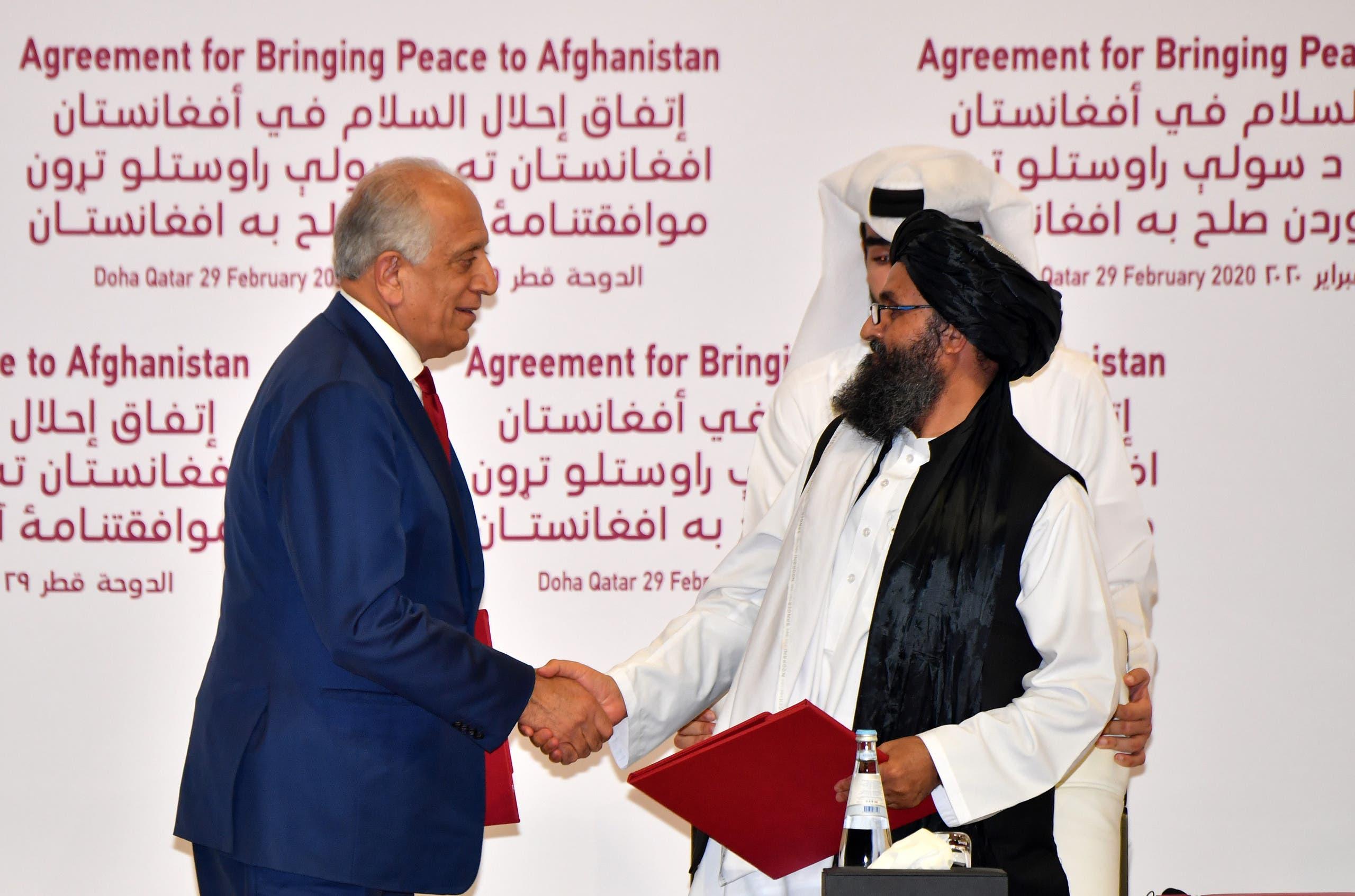 زلماي خليل زاد  يصافح أحد كبار مسؤولي طالبان خلال توقيع الاتفاق في الدوحة في فبراير الماضي