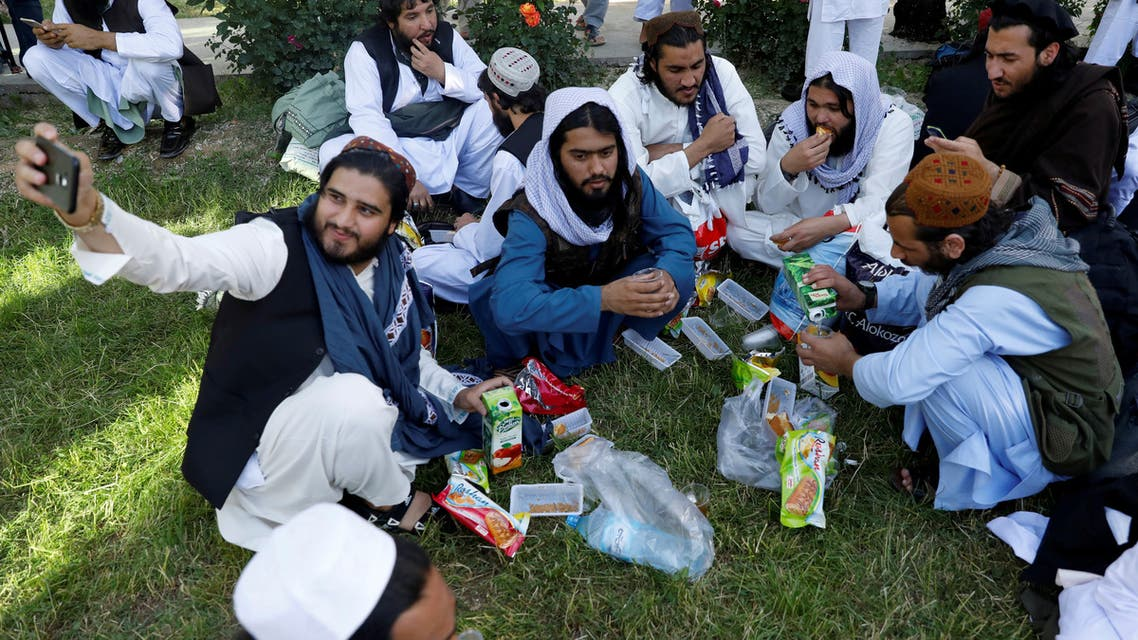 FILE PHOTO: A newly freed Taliban prisoner takes a selfie as other have juice and biscuits at Pul-i-Charkhi prison, in Kabul, Afghanistan May 26, 2020. REUTERS/Mohammad Ismail/File Photo