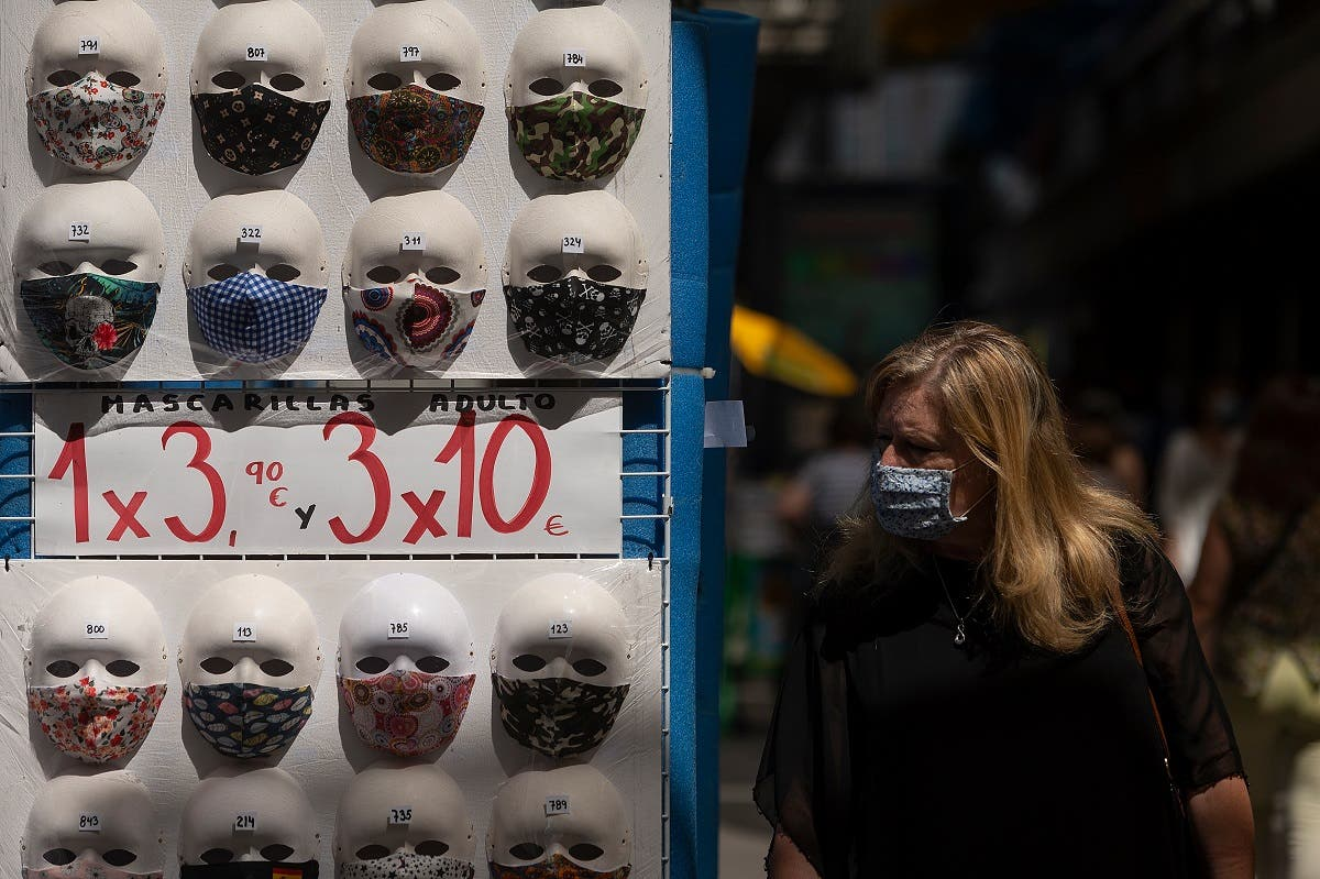 A woman wearing a face mask walks past a display of masks on sale at a shop in the center of Madrid on July 29, 2020. (AFP)