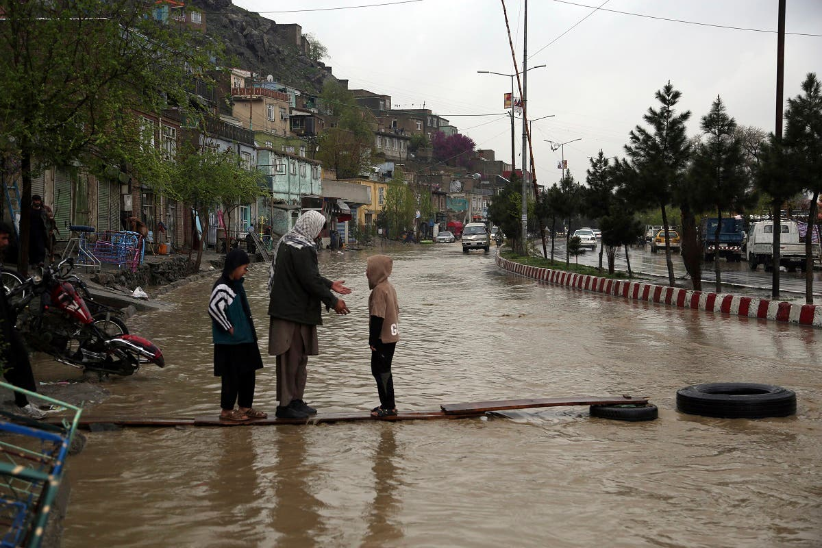An Afghan man walks with his children through floodwaters as heavy rain falls in Kabul, Afghanistan, Tuesday, April 16, 2019. (AP)