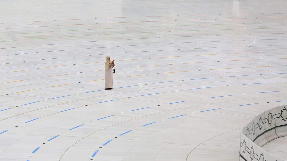 A mask-clad woman stands on a ring delineating where worshippers be around the Kaaba, Islam's holiest shrine, due to the COVID-19 coronavirus pandemic at the almost empty Grand Mosque in Saudi Arabia's holy city of Mecca. (AFP)