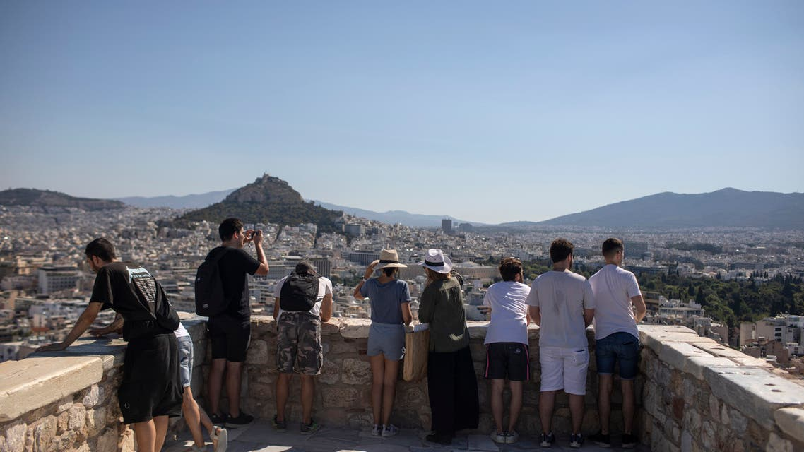 Tourists explore at Acropolis Hill, in Athens, Friday, July 31, 2020. Greece cautiously reopened its tourism industry, despite tough new coronavirus restrictions that came into force this week. Most of the new restrictions are unrelated to tourism. (AP Photo/Petros Giannakouris)