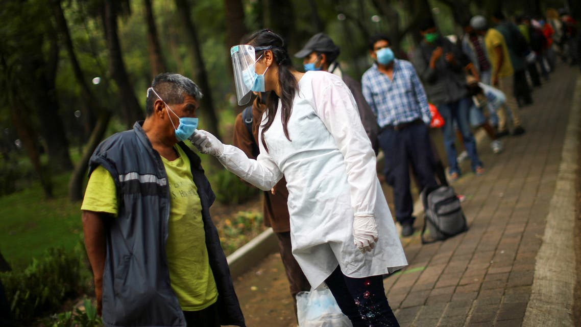 A medical staff scans the temperature of a man lining up for free food at a public park, as the outbreak of the coronavirus disease (COVID-19) continues in Mexico City, Mexico, July 30, 2020. REUTERS/Edgard Garrido