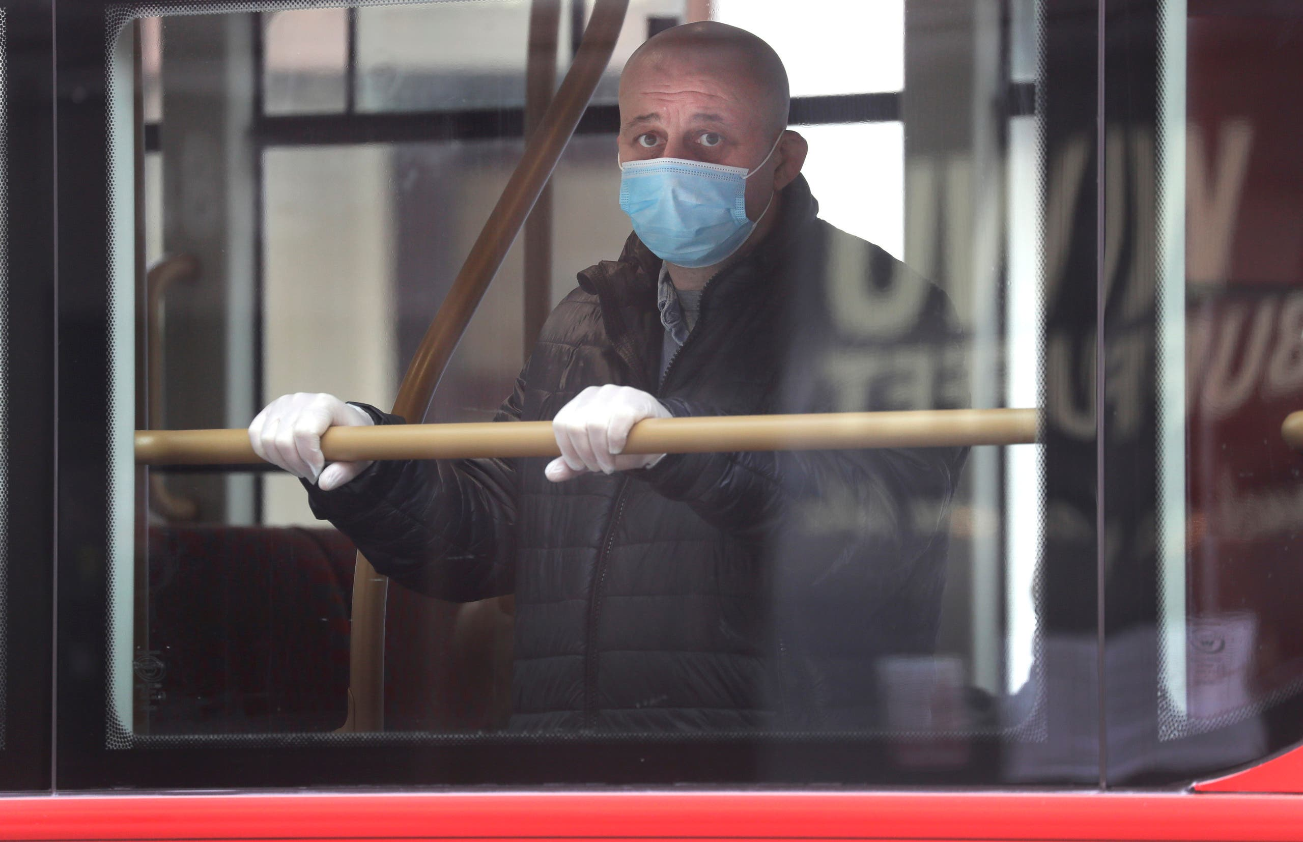 A man wears a mask to protect against the coronavirus as he looks out of the window of a bus in London on May 4, 2020. (AP)