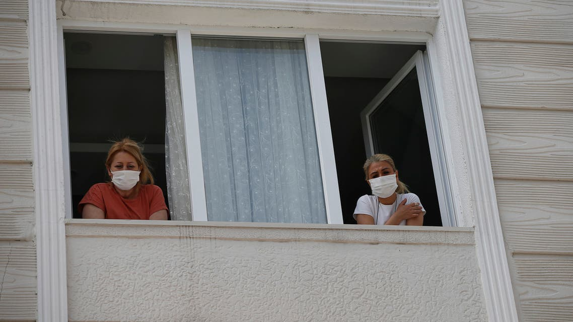 Betul Sahbas, 47, right, who had been experiencing COVID-19 symptoms, looks from her window in Istanbul on May 15, 2020. (AP)