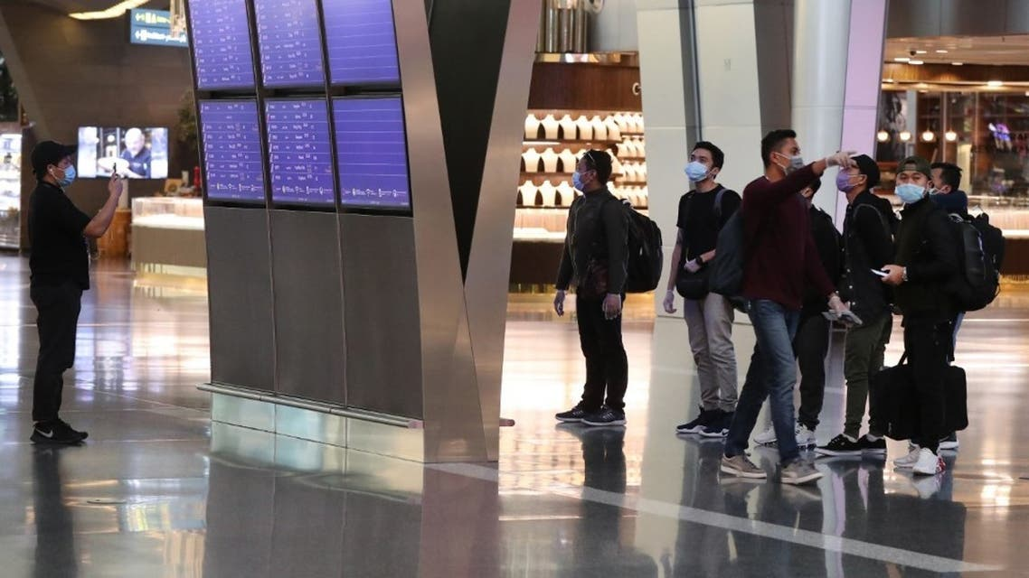 Travellers wearing face masks, due to the COVID-19 coronavirus pandemic, check their flights on information displays at Hamad International Airport in the Qatari capital Doha on April 1, 2020. (AFP)
