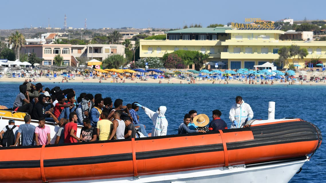 Migrants from Tunisia and Lybia are examined as they arrive onboard of an Italian Guardia Costiera (Coast Guard) boat in the Italian Pelagie Island of Lampedusa, while a beach with tourists is seen in the background, on August 1, 2020. AFP