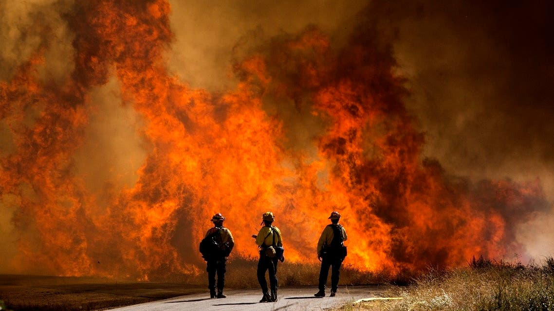 Firefighters watch as flames flare at the Apple Fire in Cherry Valley, California, Saturday, August 1, 2020. (AP)