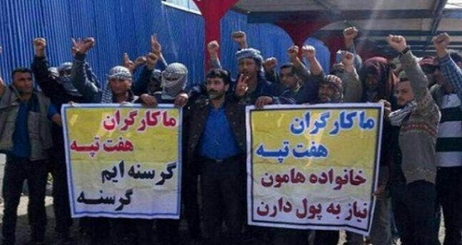 """An undated photo of workers from the Haft-Tappeh Sugarcane Company with placards that read """"our families need money"""" and """"we are starving."""" (Twitter: @amirali872712)"""