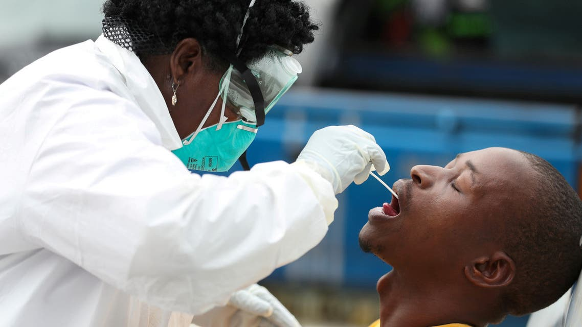 FILE PHOTO: A member of medical staff swabs the mouth of a resident as she is testing him for a virus, during a nationwide lockdown for 21 days to try to contain the coronavirus disease (COVID-19) outbreak, in Alexandra, South Africa, March 31, 2020. Picture taken March 31. 2020. REUTERS/Siphiwe Sibeko/File Photo