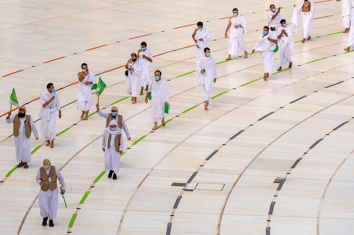 Muslim pilgrims wearing face masks and keeping social distance perform Tawaf around Kaaba during the annual Haj pilgrimage. (Reuters)
