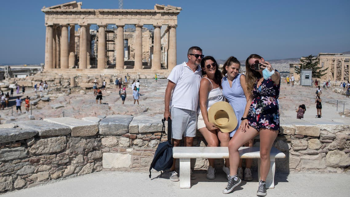 A French family takes a selfie in front of the ancient Parthenon temple in Athens on July 31, 2020. (AP)