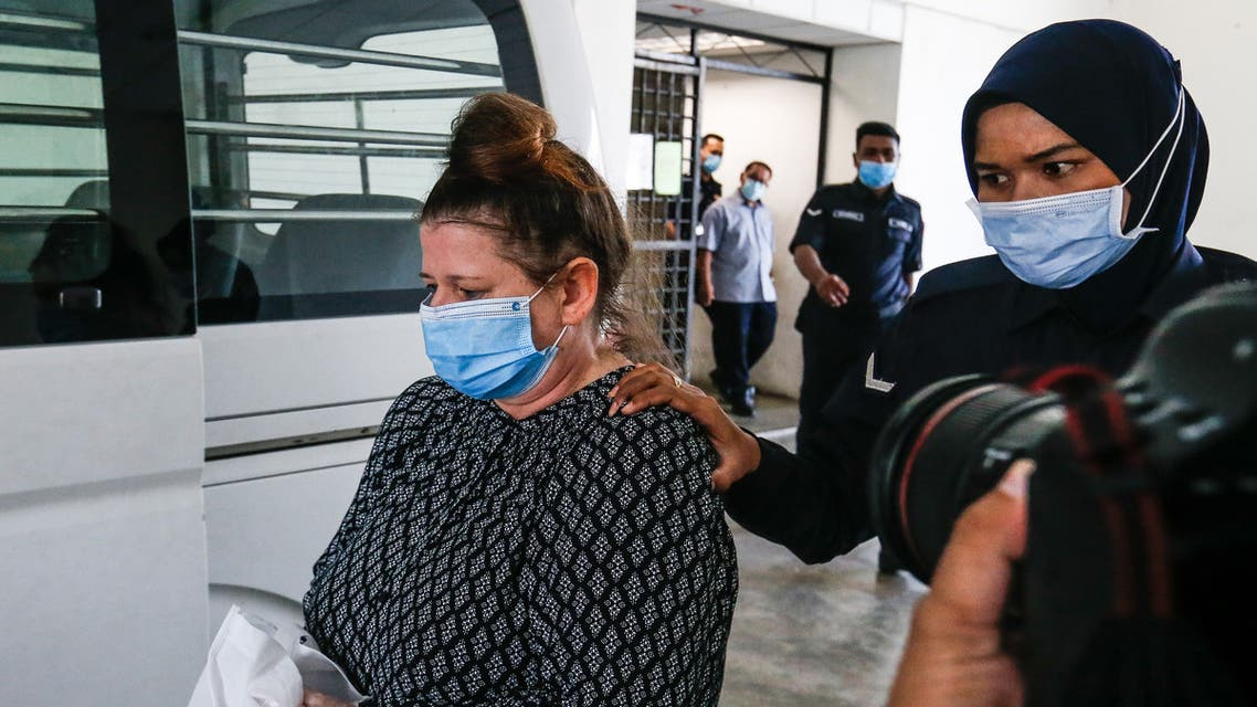 British national Samantha Jones, accused of killing her husband in 2018, is escorted by a police officer to a van after appearing in court in Alor Setar, in northern Malaysia, on August 3, 2020. (AFP)