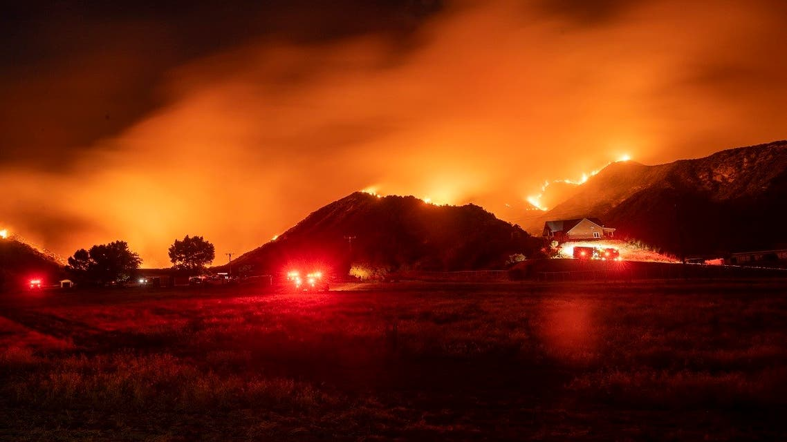 In this long exposure photograph, firefighters monitor flames as they skirt a hillside near a residential area during the Apple fire in Banning, California on August 1, 2020. (AFP)