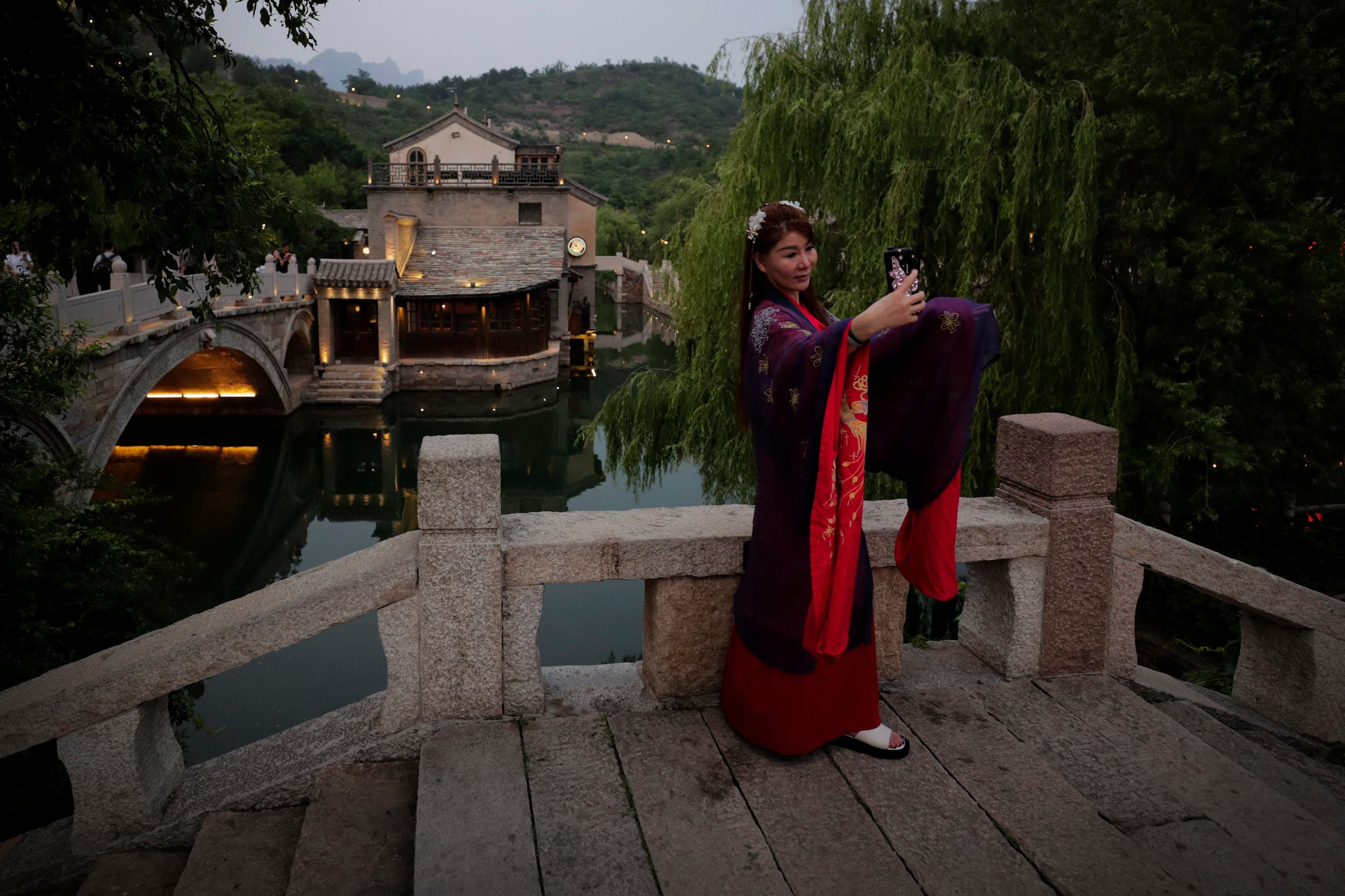 A woman wearing traditional clothing takes a selfie at the ancient village in Gubei Water Town, a popular tourist spot in Beijing, Tuesday, June 9, 2020. (AP)
