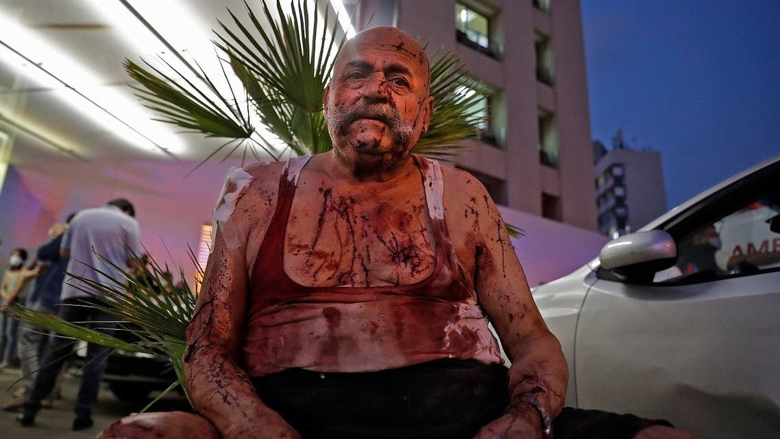 A wounded man receives help outside a hospital following an explosion in the Lebanese capital Beirut on August 4, 2020. (AFP)