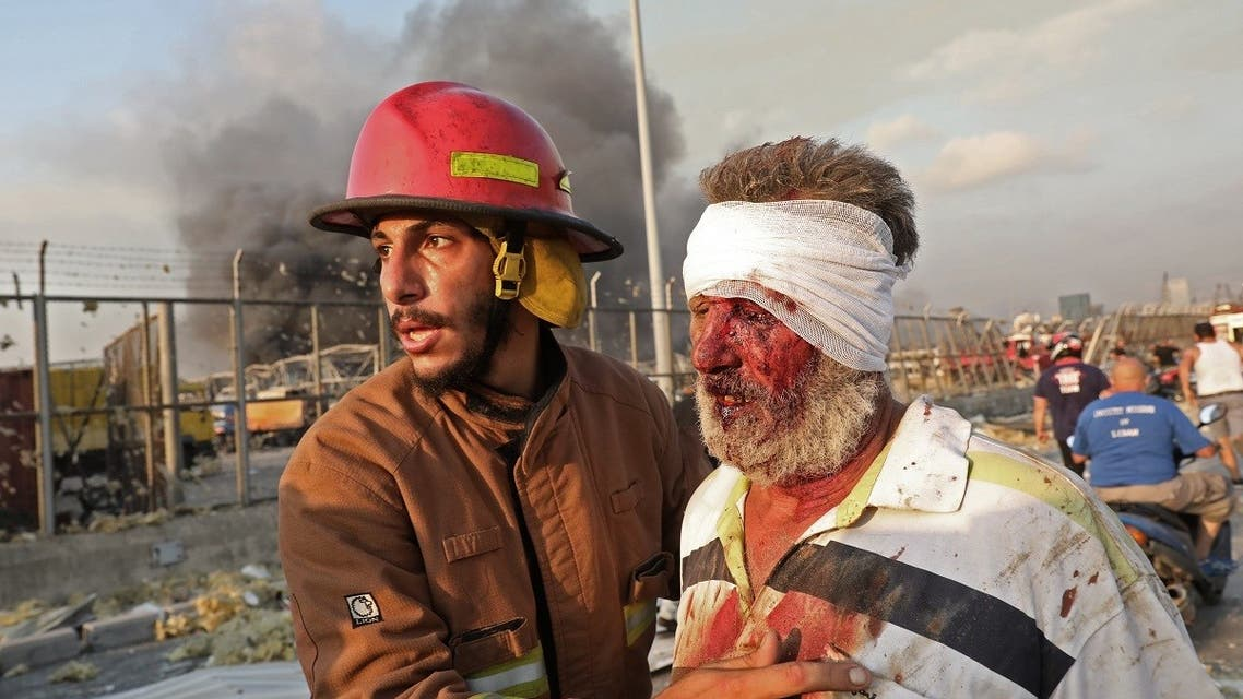 A wounded man is helped by a fireman near the scene of an explosion in Beirut on August 4, 2020. (AFP)