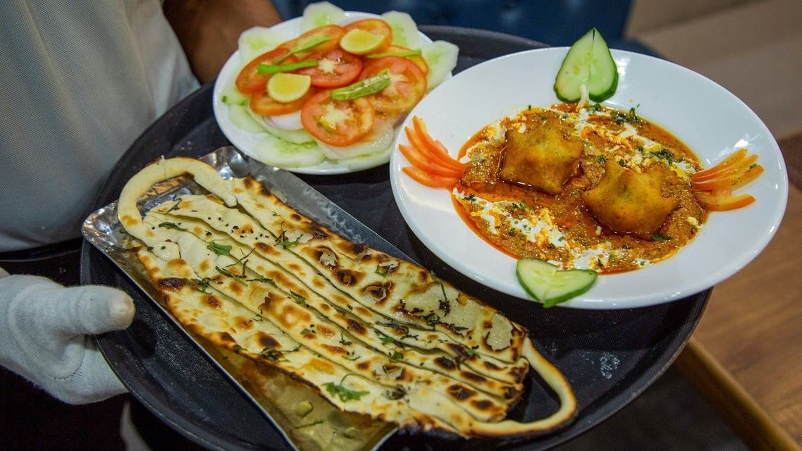 A waiter carries 'Covid Curry' and 'Mask Naan,' two Covid-19 coronavirus-themed dishes, to serve to customers at their restaurant in Jodhpur on August 3, 2020. (AFP)