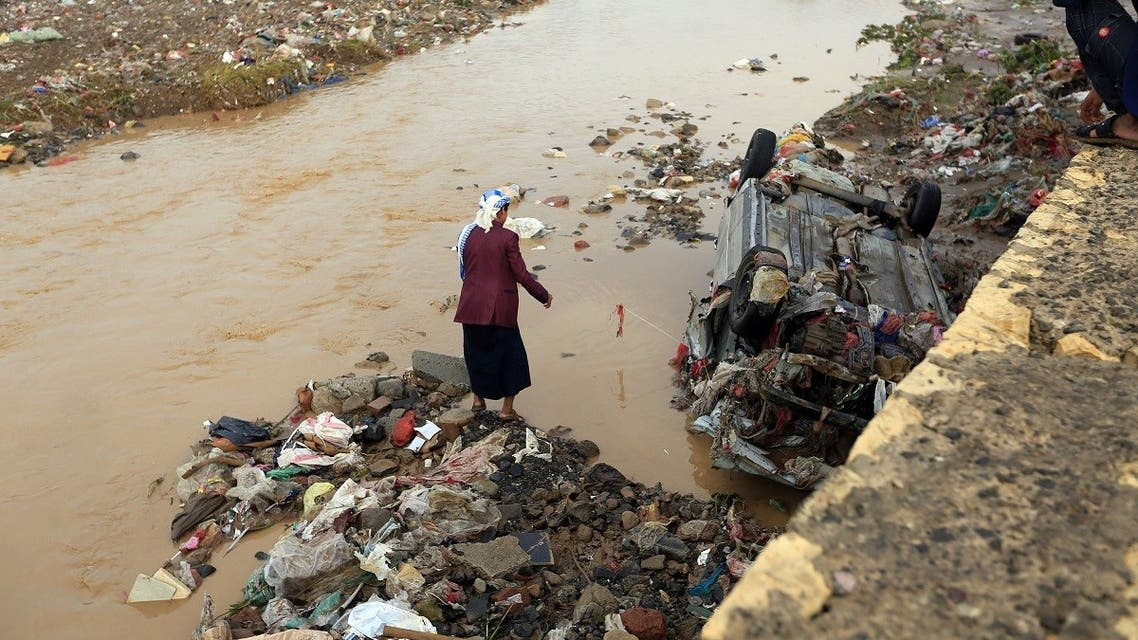 Yemenis check out a destroyed car under an overpass after it was overtaken by floods following heavy rains in the capital Sanaa, on April 14, 2020. (AFP)