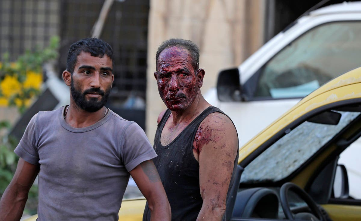 Wounded people walk near the scene of an explosion in Beirut on August 4, 2020. (AFP)