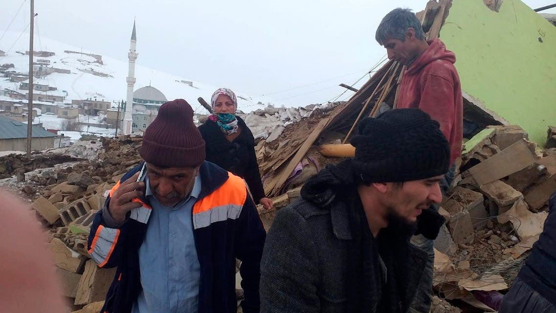 People stand on the debris of their collapsed house after an earthquake hit villages in Baskale town in Van province, Turkey, at the border with Iran. (File photo: AP)