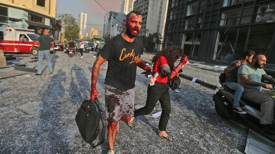 Wounded people walk near the site of an explosion at the port in the Lebanese capital Beirut on August 4, 2020. (AFP)