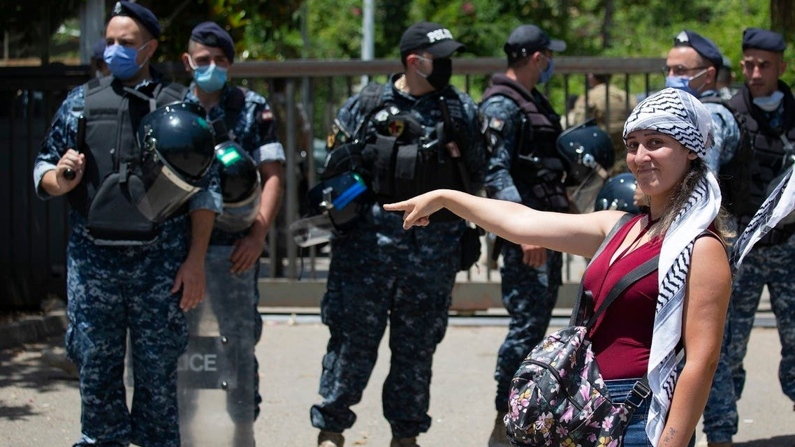 An anti-government protester points to Lebanese riot police after scuffling outside the Ministry of Energy and Water in Beirut, Lebanon, Thursday, May 21, 2020. (AP)