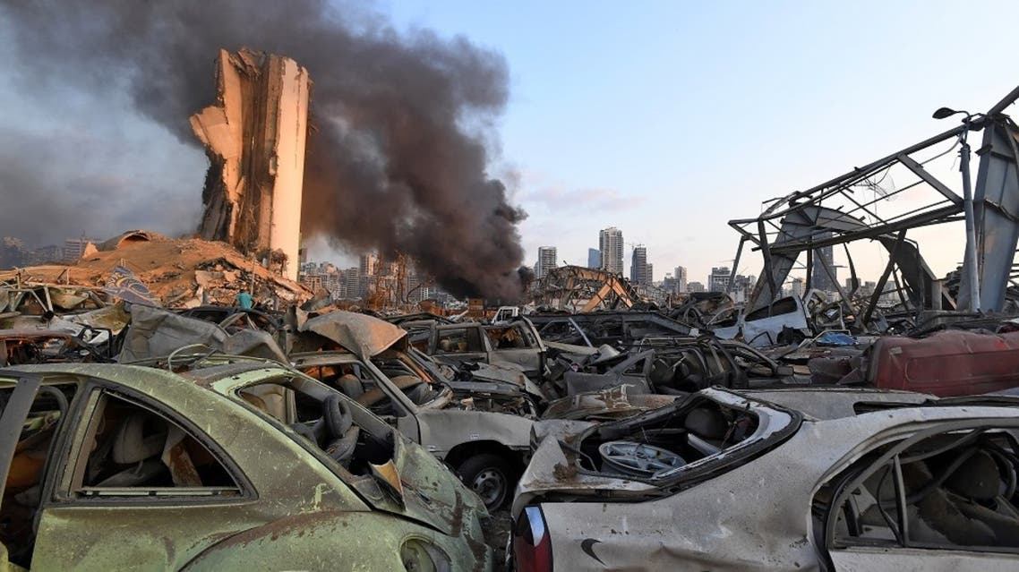 Damaged cars are pictured in front of billowing smoke behind the grain silos at the port of Beirut following a massive explosion that hit the heart of the Lebanese capital on August 4, 2020. (AFP)