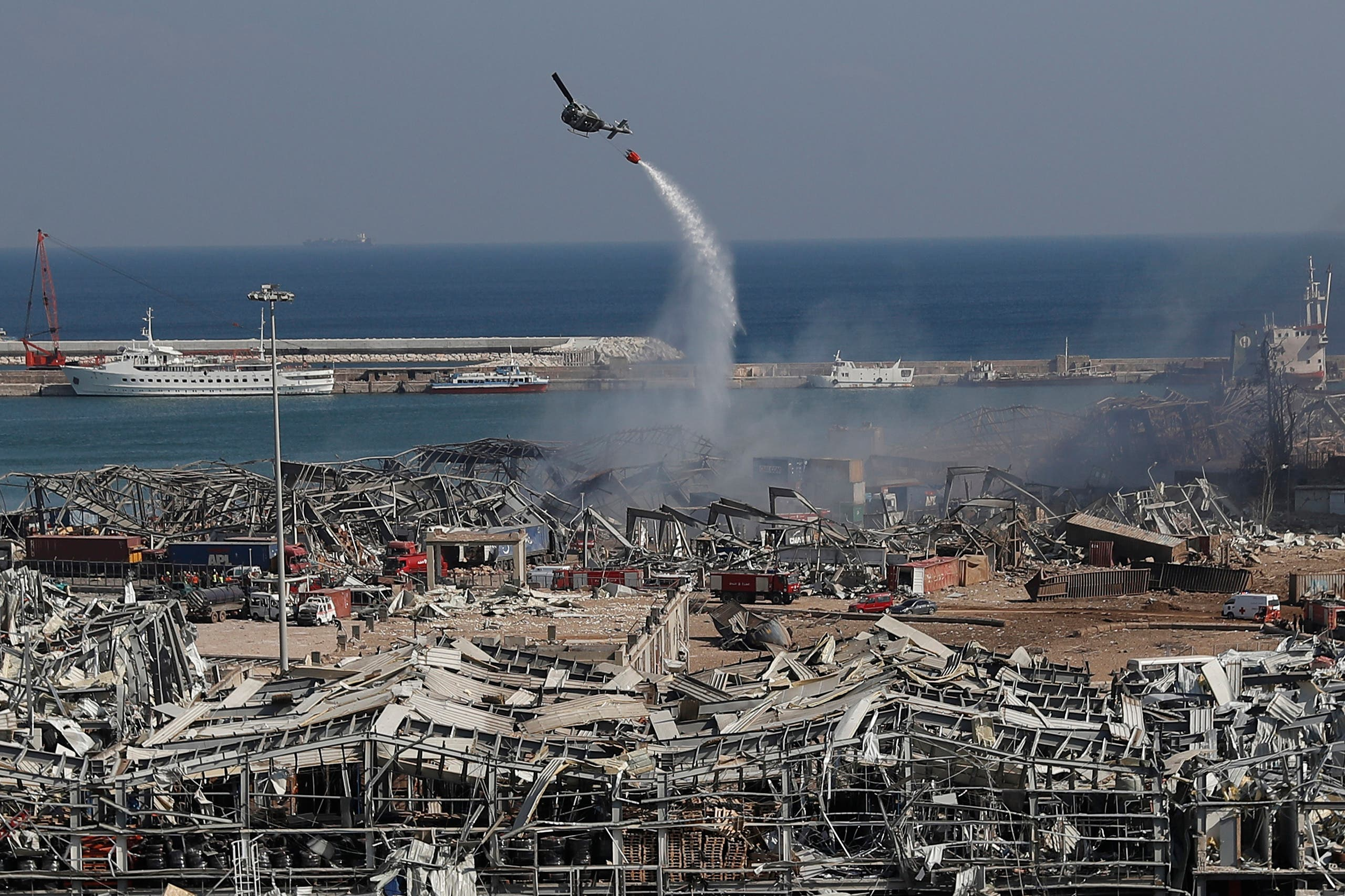 An army helicopter drops water at the scene of Tuesday's massive explosion that hit the seaport of Beirut on August 5, 2020. (AP)