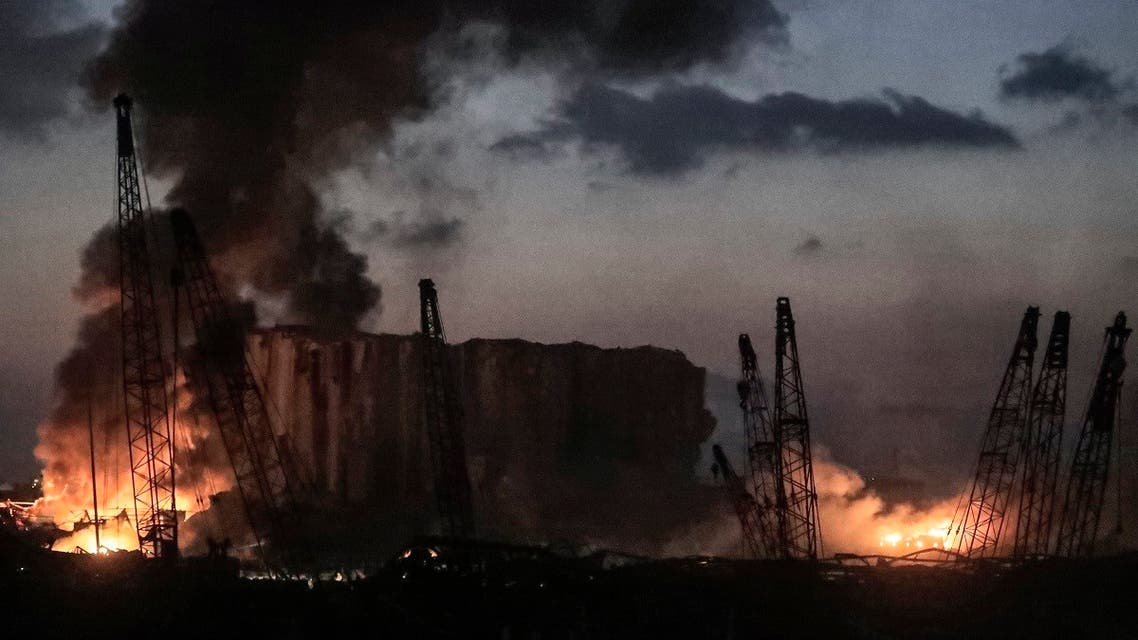 This picture taken on August 4, 2020 shows fires burning at the port of Lebanon's capital Beirut with its cranes in the aftermath of a massive explosion. (AFP)