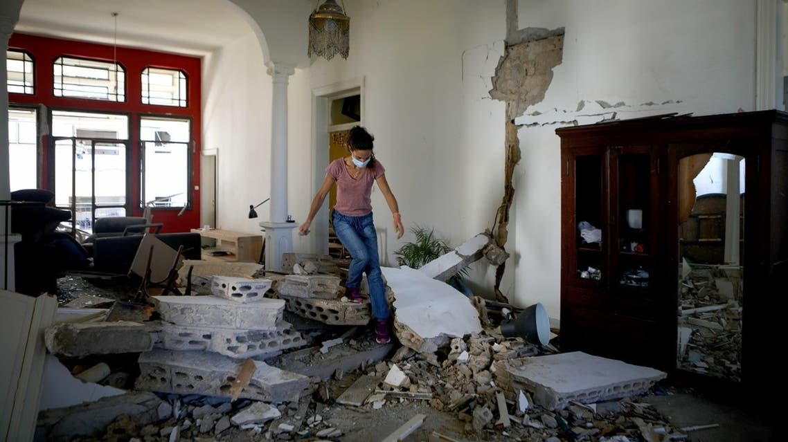 A Lebanese woman walks over the rubble in her apartment in the neighborhood of Gemmayze on August 5, 2020, a day after a blast in Beirut killed more than 100 people and wounded over 5,000. (AFP)