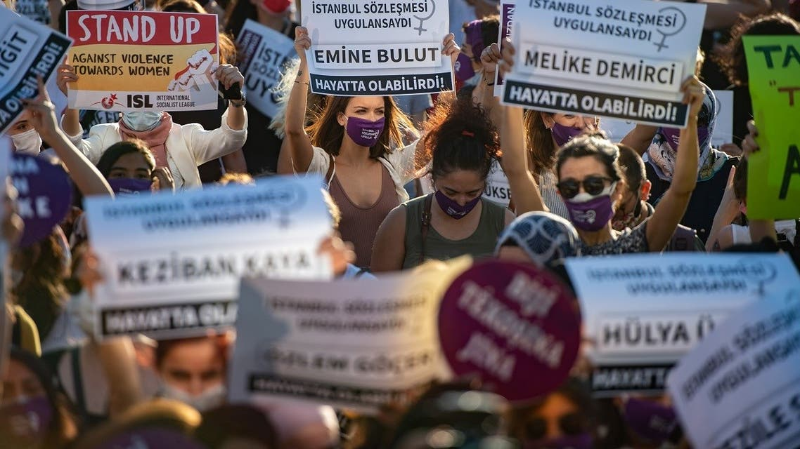 Demonstrators wearing protective face masks hold up placards during a demonstration for a better implementation of the Istanbul Convention to prevent and combat violence against women, in Istanbul, Turkey, on August 5, 2020. (AFP)