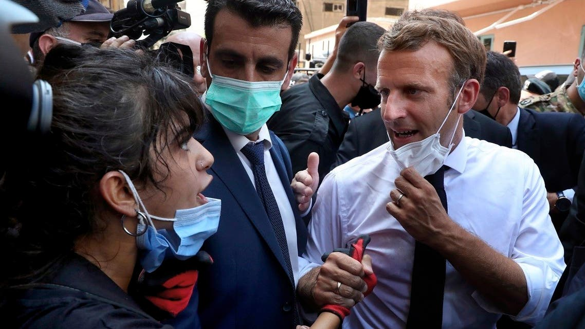 French President Emmanuel Macron, right, speaks with a woman as he visits the Gemmayze neighborhood, which suffered extensive damage from an explosion, Aug. 6, 2020. (AP)