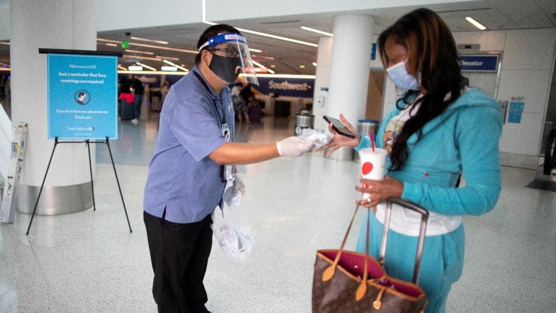 Airport employee hands out a face masks to an airline passenger at LAX airport, amid the coronavirus pandemic, in Los Angeles, California, US, August 4, 2020. (Reuters)